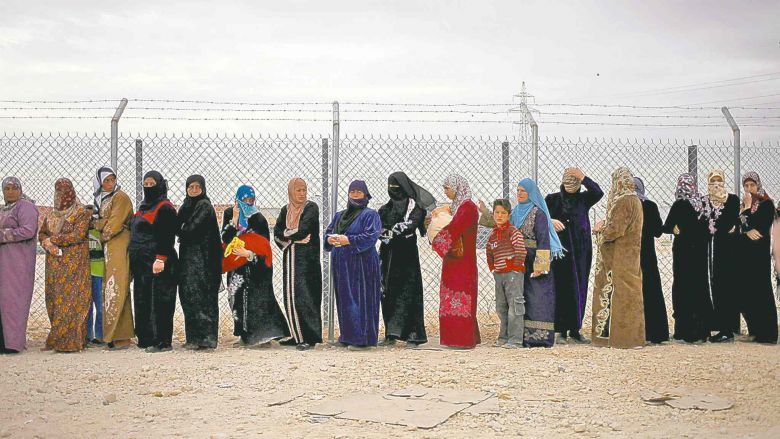 mohammad hannon / the associated press Syrian refugee women stand in line to receive their familyÕs share of winter aid kits at the Zaatari refugee camp.