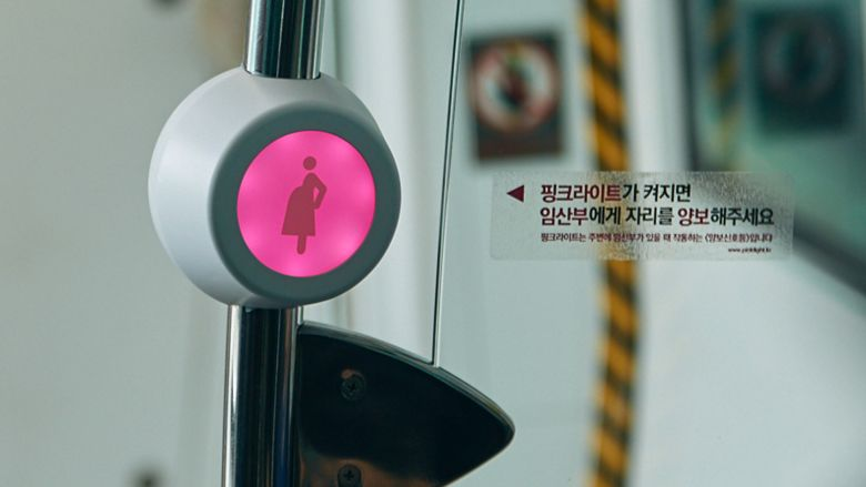 In this Wednesday, April 6, 2016 photo provided by Busan Metropolitan City, a wireless sensor attached on a metal bar next to special priority seats blinks with pink light, signaling that a pregnant passenger is approaching or standing nearby, in a subway train in Busan, South Korea. South Korea's second-largest city of Busan is testing a wireless technology it hopes can alleviate such problems and perhaps help address one of the biggest challenges facing the Asian country: a stubbornly low birthrate. (Kwon Sung-hoon/Busan Metropolitan City via AP)