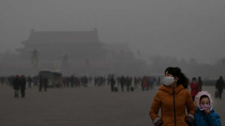 BEIJING, CHINA - JANUARY 23:  A tourist and her daughter wearing the masks visit the Tiananmen Square at dangerous levels of air pollution on January 23, 2013 in Beijing, China. The air quality in Beijing on Wednesday hit serious levels again, as smog blanketed the city.  (Photo by Feng Li/Getty Images)