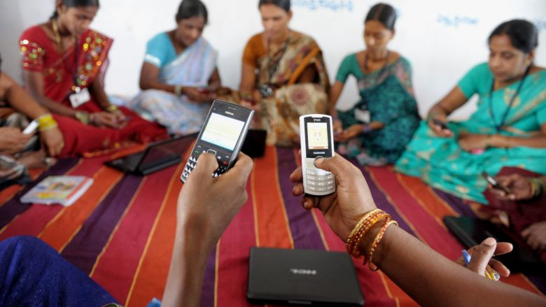 Indian villagers, part of a Self Help Group (SHG) organisation, pose with mobile phones and laptops in Bibinagar village outskirts of Hyderabad on March 7, 2013, on the eve of International Women's day. Members of SHG's make small regular savings contributions over a few months until there is enough capital in the group to begin lending, and they use their mobiles and laptops to record financial transactions. SHG's are seen as instruments for a variety of goals including empowering women, developing leadership abilities among poor people, increasing school enrolments, and improving nutrition and the use of birth control.  AFP PHOTO / Noah SEELAM        (Photo credit should read NOAH SEELAM/AFP/Getty Images)